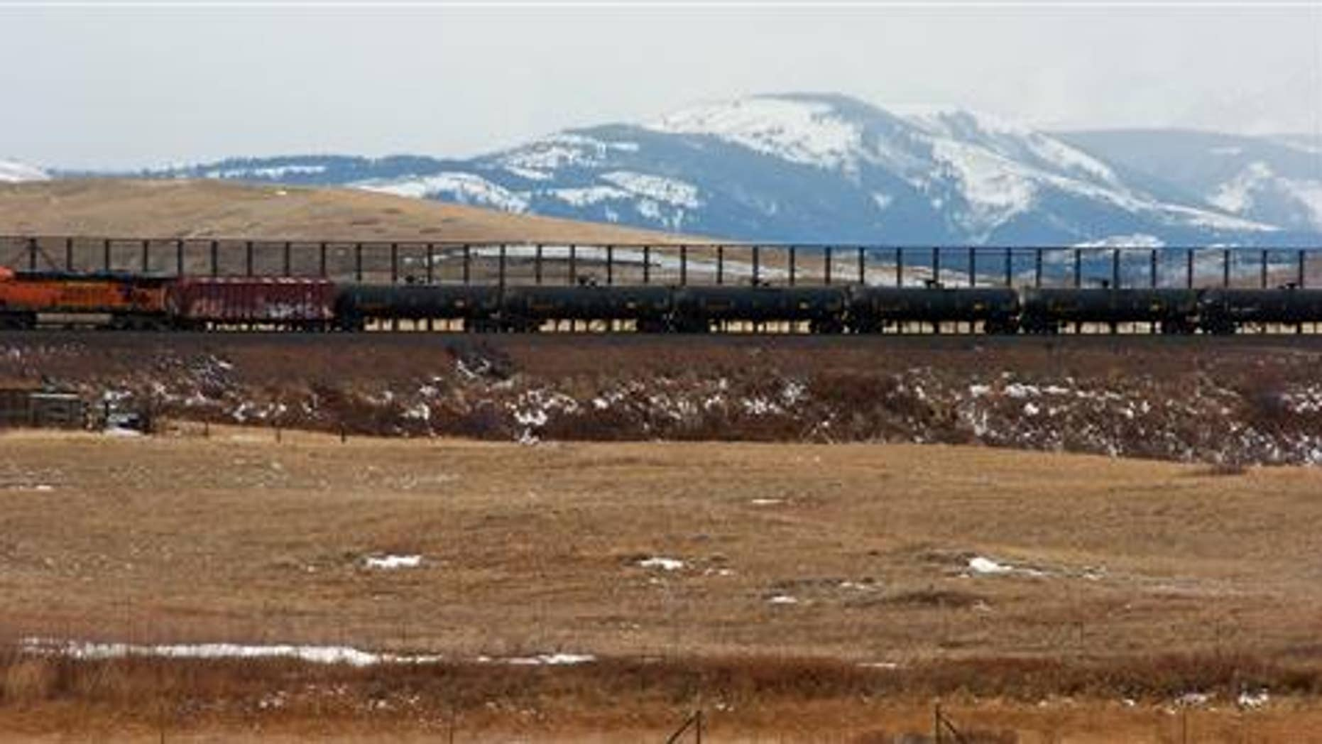 In this Nov. 7, 2013, photo, a train hauls oil into Glacier National Park near the Badger-Two Medicine National Forest in northwest Montana. Companies proposing to build the nation's largest oil-by-rail marine terminal in southwest Washington State and their foes will argue their cases before a state energy panel in Vancouver, Wash., on Monday, June 27, 2016. (AP Photo)