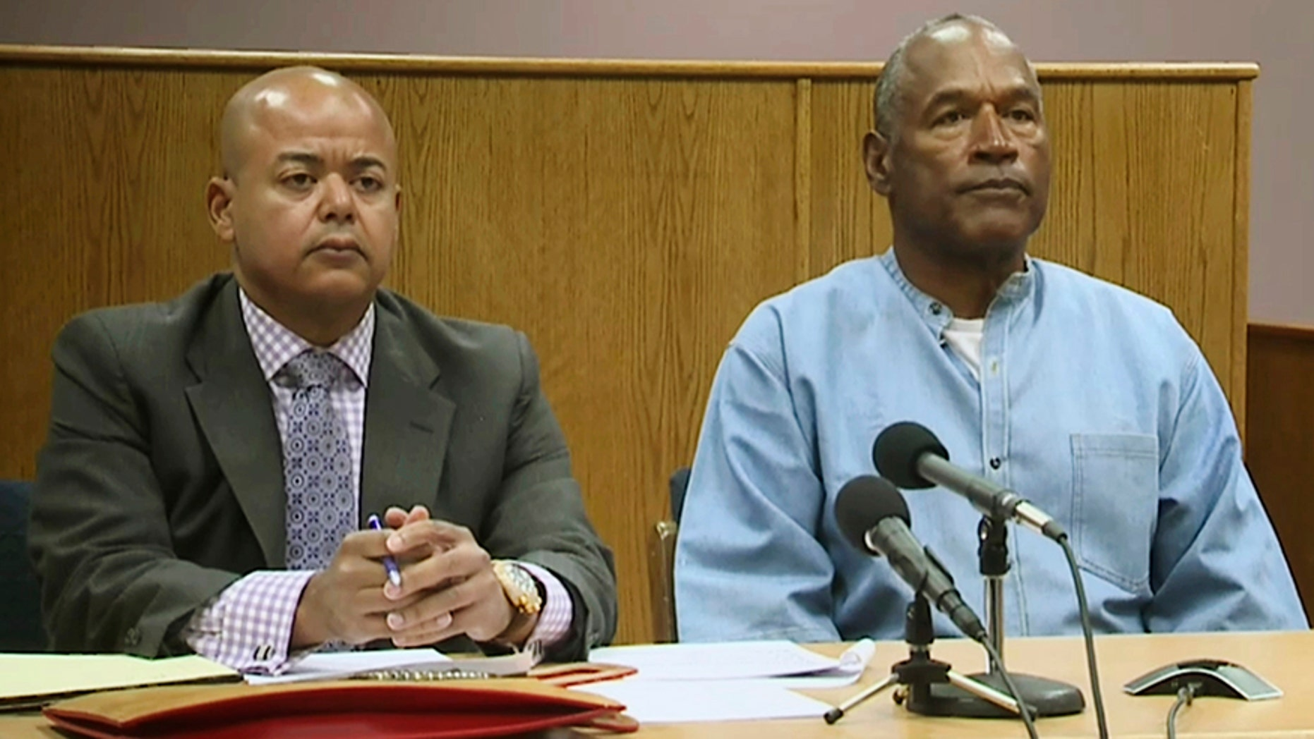 Former NFL football star O.J. Simpson appears with his attorney, Malcolm LaVergne, left, via video for his parole hearing at the Lovelock Correctional Center in Lovelock, Nev.
