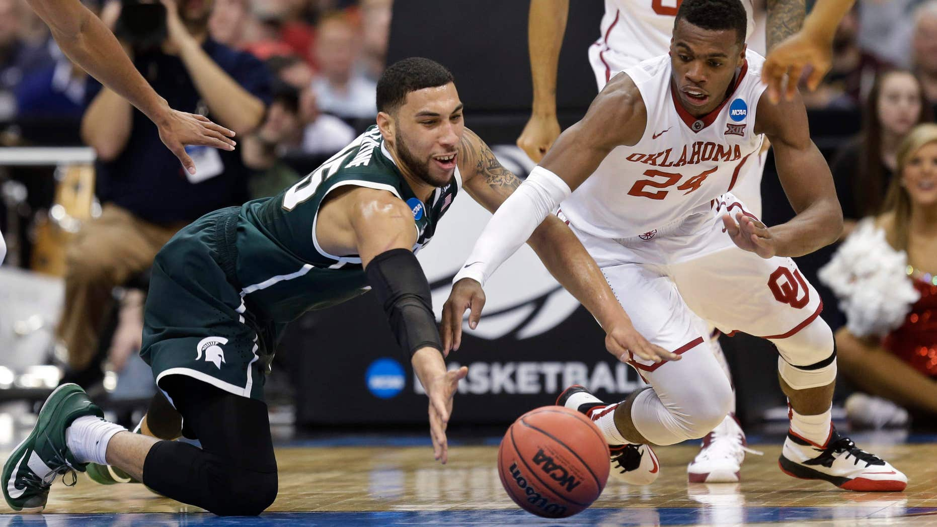 March 27, 2015: Michigan State's Denzel Valentine (45) and Oklahoma's Buddy Hield (24) dive for the ball during the first half of a regional semifinal in the NCAA men's college basketball tournament .