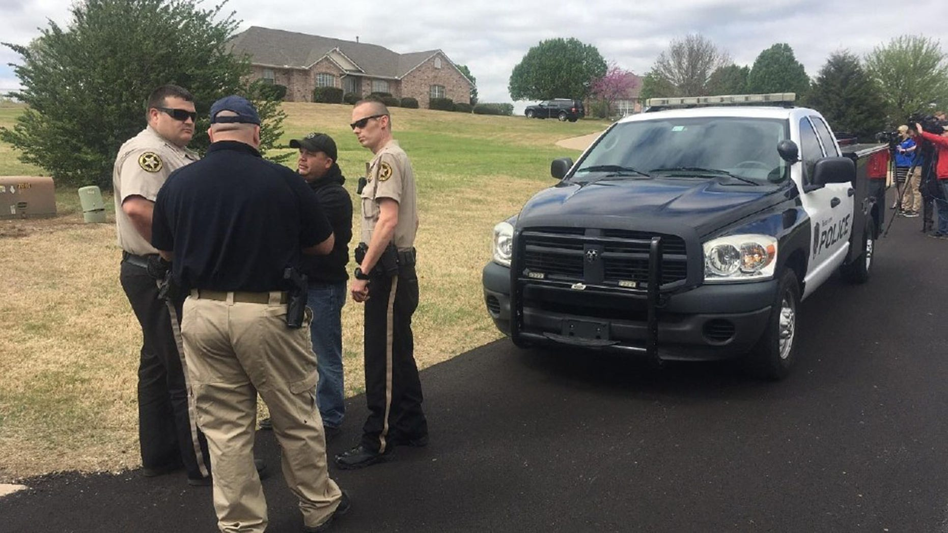 Sheriff's deputies gather outside a home in Broken Arrow, Okla., where three intruders were shot and killed Monday, March 27, 2017.