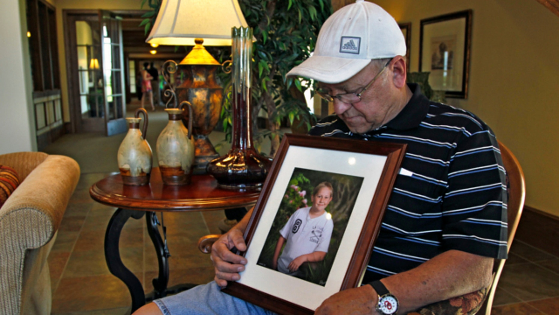 May 22, 2013: Marvin Dixon, the grandfather of 8-year-old tornado victim Kyle Davis, glances down at a photo of his grandson while sitting for a portrait in the lobby of a funeral home where his grandson awaits burial, in Oklahoma City.