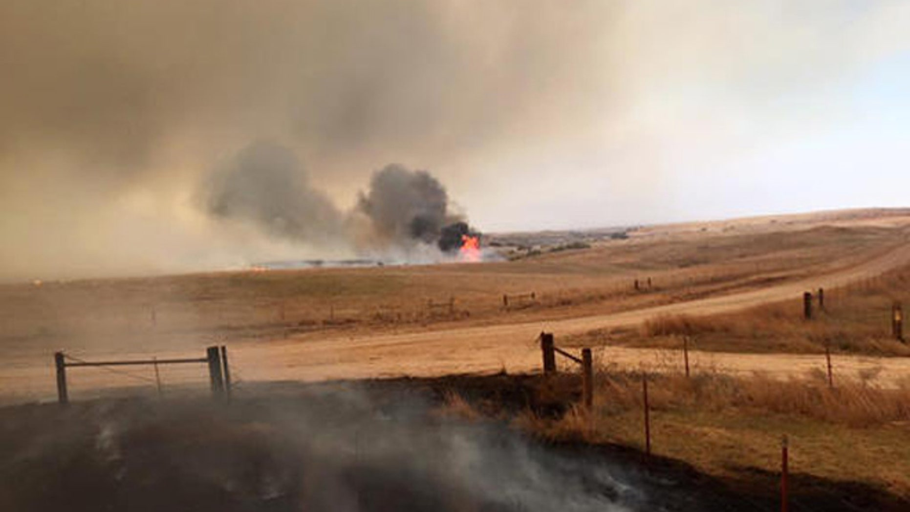 This April 5, 2016 photo provided by Landon Cates, volunteer firefighters from the Dewey County Task Force work a blaze southwest of Freedom, Okla. Oklahoma Forestry Services Director George Geissler says arcing power lines are to blame for the blaze in northwest Oklahoma, located about 170 miles northwest of Oklahoma City. (Landon Cates/Leedy Fire Department via AP)