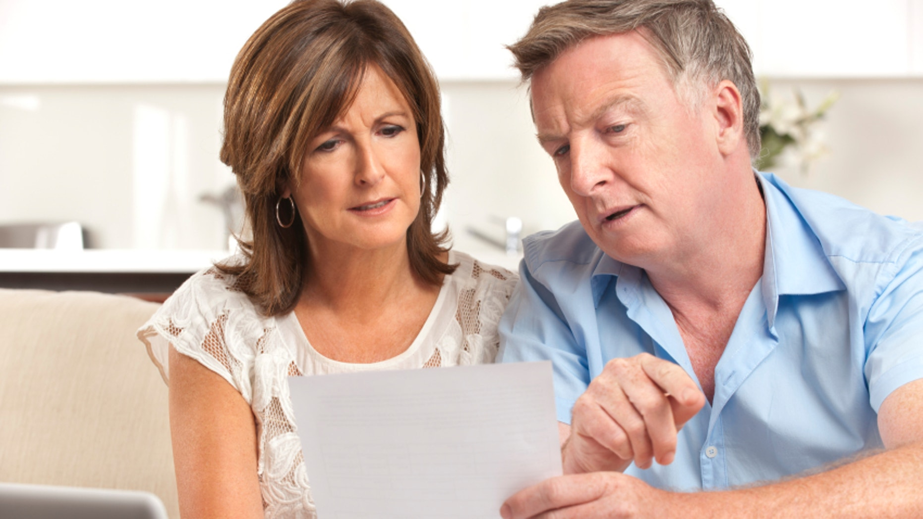 Mature couple worrying about finances at home