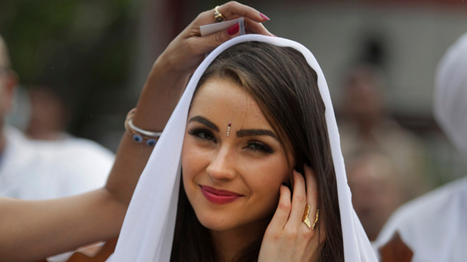 Sept. 30, 2013: Miss Universe, Olivia Culpo of the USA, watches a performance by inmates as designer Sanjana Jon, adjusts her veil during a visit to the Tihar Jail in New Delhi, India. Tihar is a massive complex of nine separate jails in New Delhi that is one of the largest incarceration facilities in South Asia.
