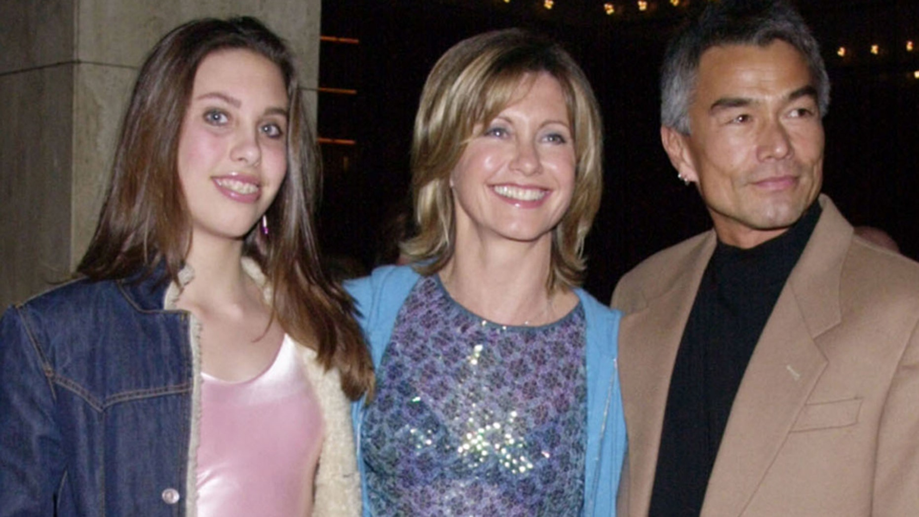 """Singer and actress Olivia Newton-John (C) poses with her daughter Chloe and Patrick McDermott upon arriving February 26, 2001 for the opening night of """"Mamma Mia!"""" at the Los Angeles Shubert Theatre. REUTERS"""