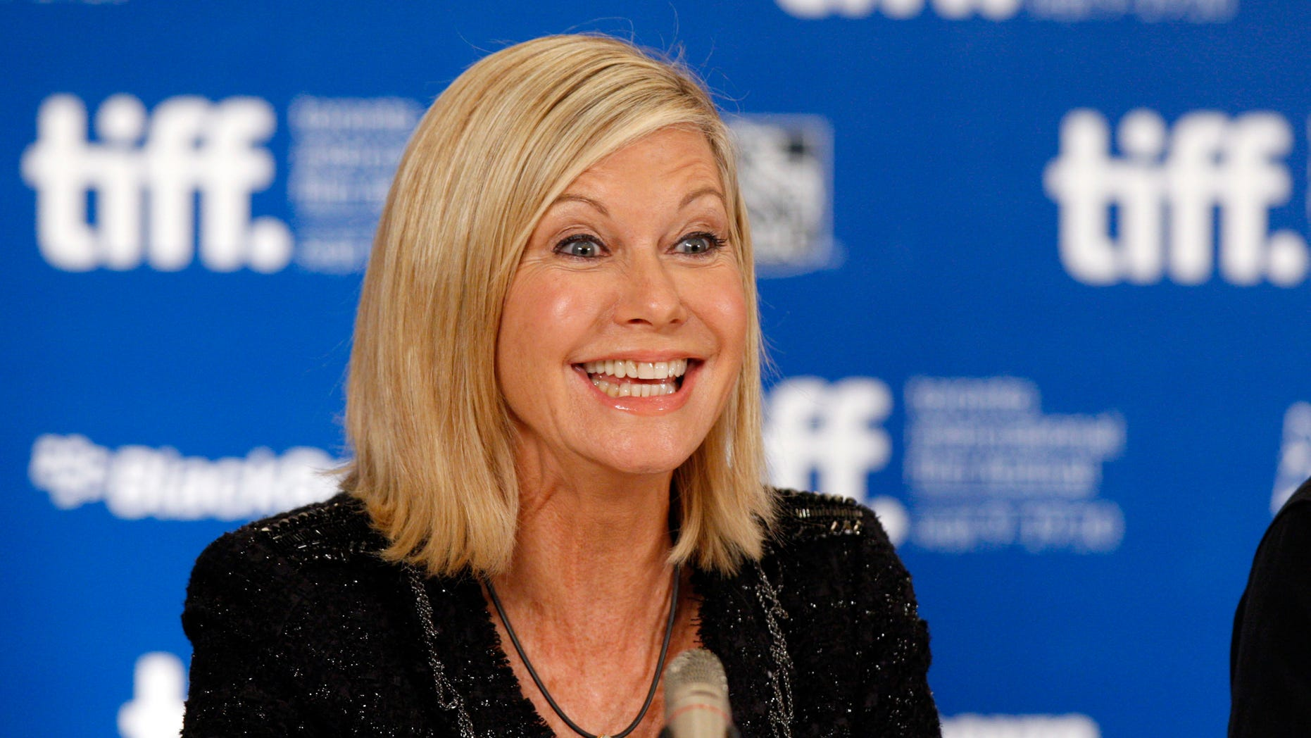 """Australian actress Olivia Newton-John smiles during the news conference for the film """"Score: A Hockey Musical"""" at the 35thToronto International Film Festival September 10, 2010.   REUTERS/Mike Cassese   (CANADA - Tags: ENTERTAINMENT PROFILE) - RTR2I5O6"""