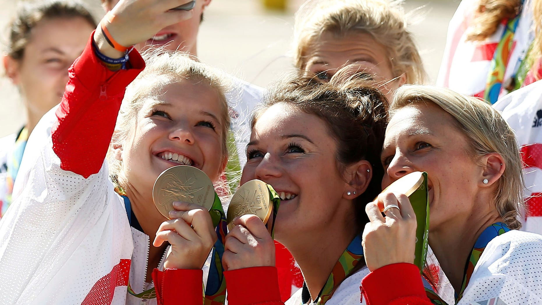 Team GB athletes pose with their medals for selfies as they return home from the 2016 Rio Olympics, at Heathrow Airport in London, Britain August 23, 2016. (REUTERS/Peter Nicholls)