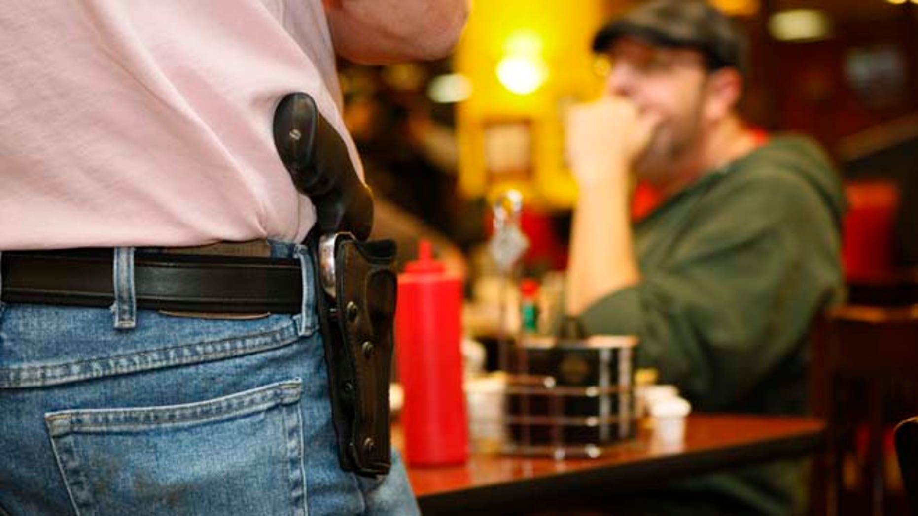 FILE: A man in Oklahoma wears an unconcealed side arm. The Texas House of Representatives on Friday voted 96-35 to allow residents with concealed-handgun licenses to openly carry their guns in public in holsters.