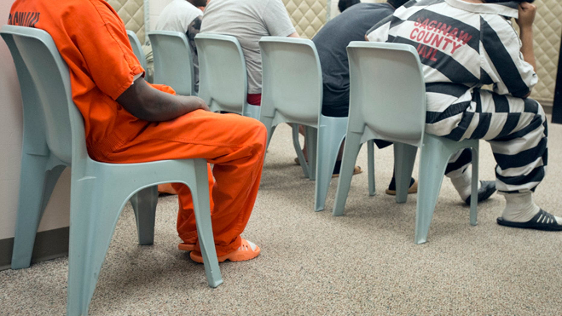 Inmates wait for their video arraignments at the Saginaw County Jail, Friday, July 18, 2014. The Saginaw County Sheriff's Department has purchased new jumpsuits, with black and white stripes, for some of the inmates at the jail. (AP Photo/The Saginaw News/MLive.com, Jeff Schrier)