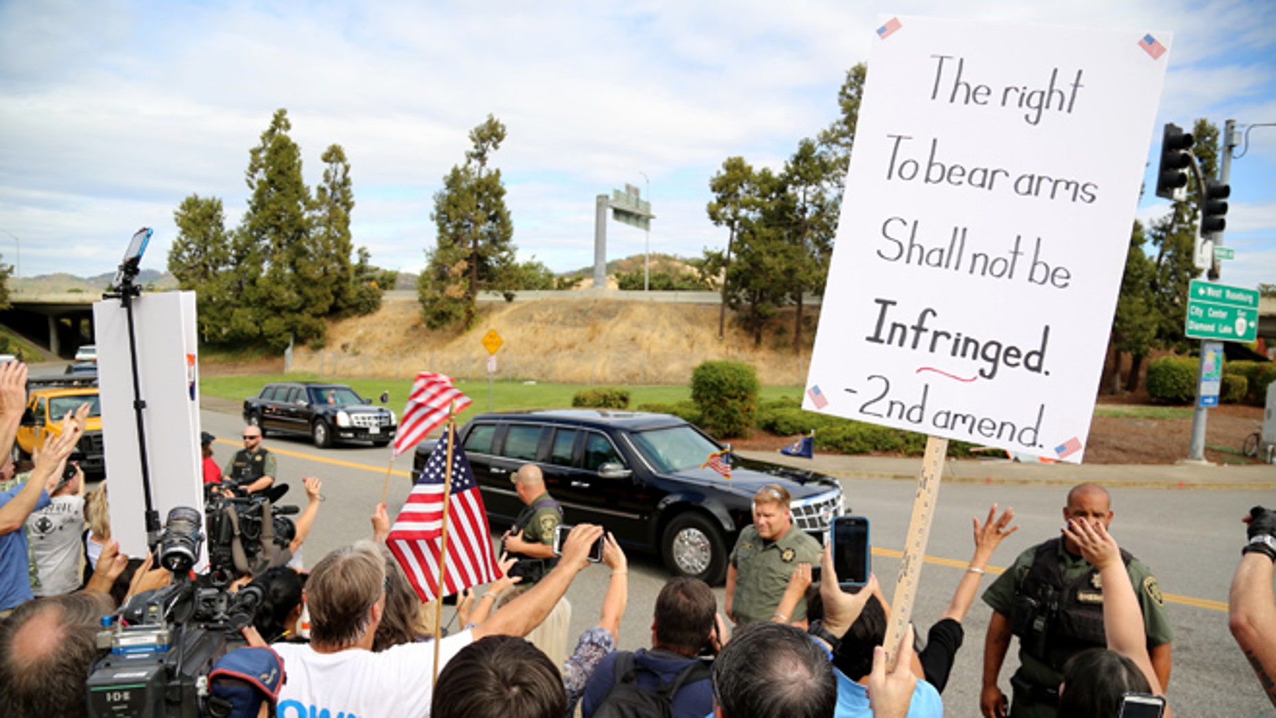 In this Oct. 9, 2015, photo, demonstrators wave flags and signs as President Obama's motorcade drives by in Roseburg, Ore.