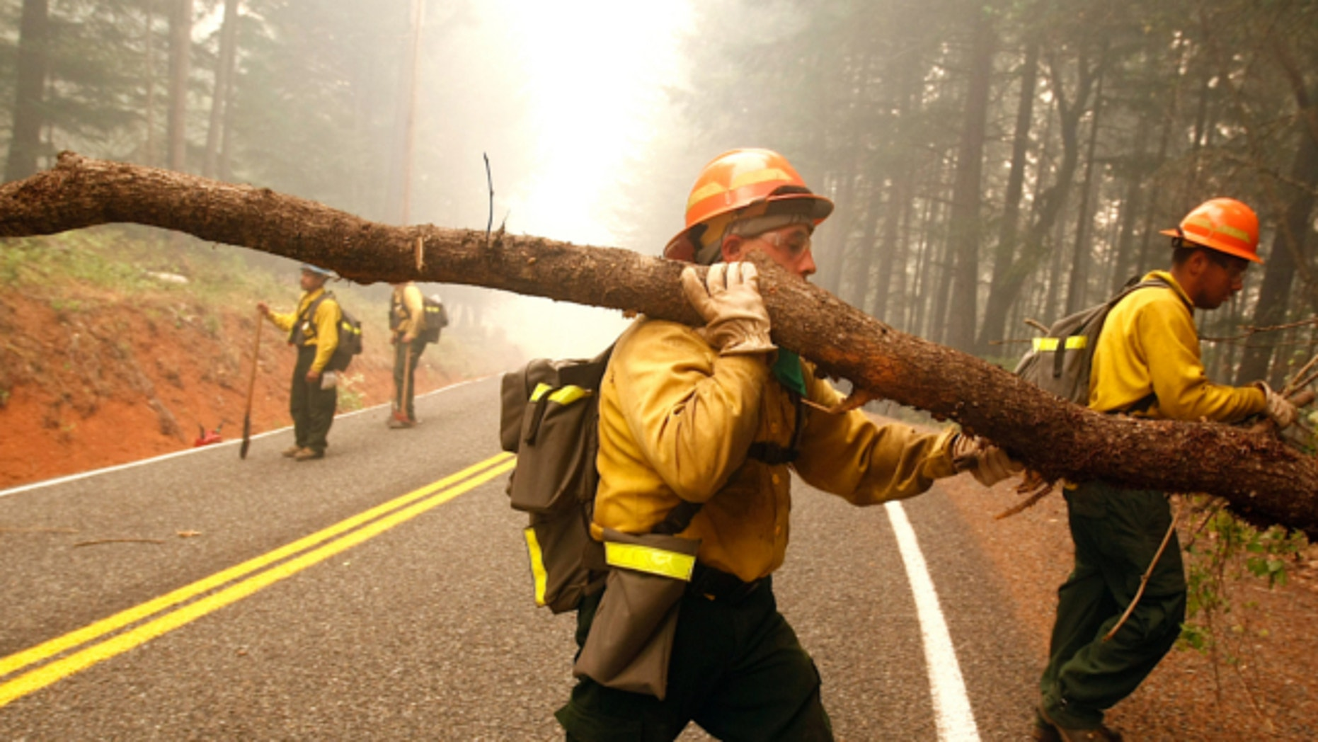 July 31, 2013: Dalles, Ore. firefighters Mario Carmona, middle, and Ismael Vega, right, help clear brush and trees near a home in Wolf Creek, Ore.