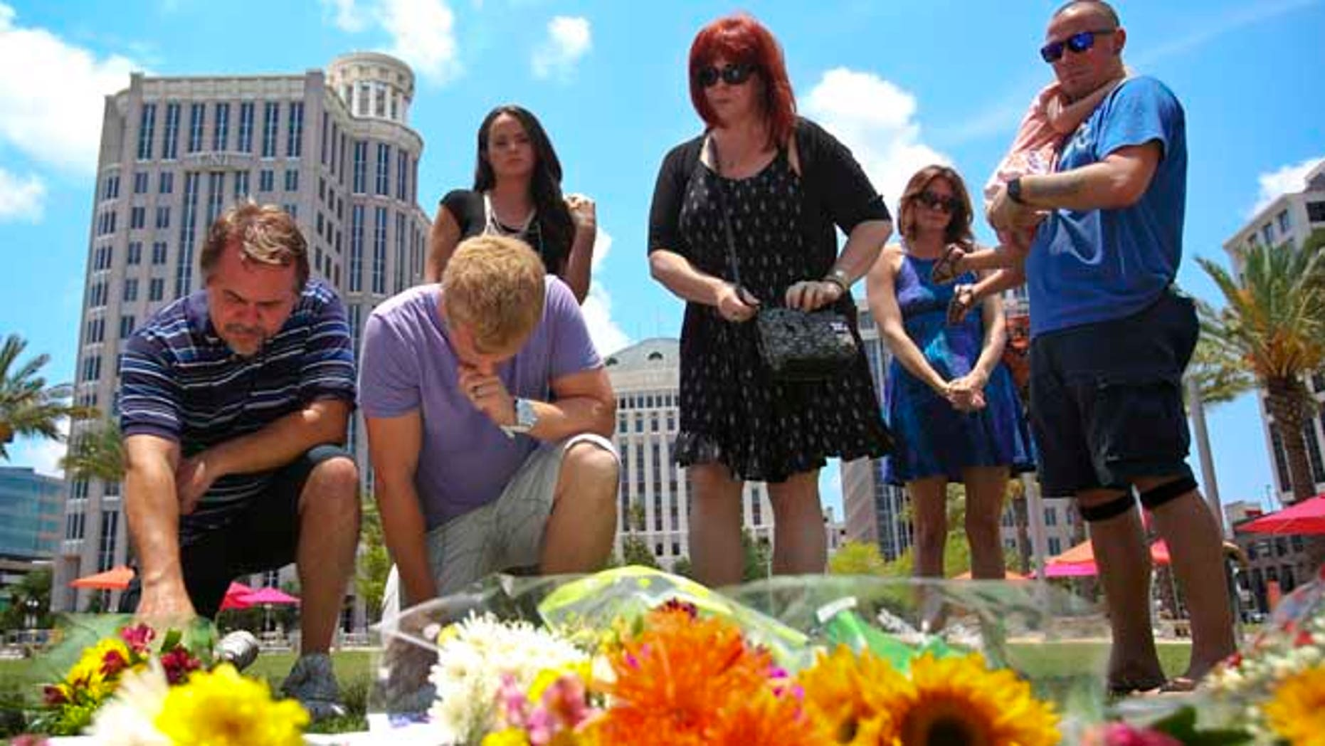 Mourners at a makeshift memorial for the victims of the Pulse nightclub shooting outside of the Dr. Phillips Performing Arts Center on Monday , June 13, 2016.