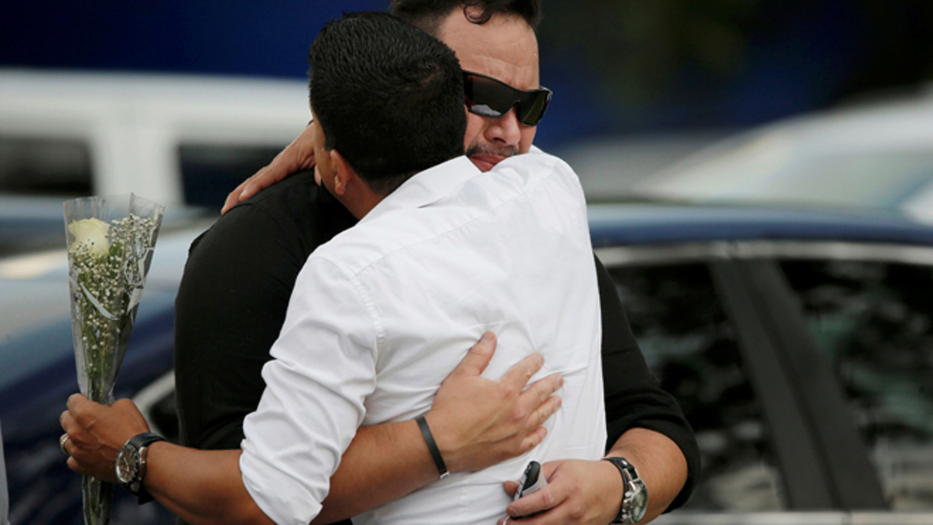 Mourners embrace outside the wake for Pulse shooting victim Javier Jorge Reyes in Orlando, Florida, U.S. June 15, 2016