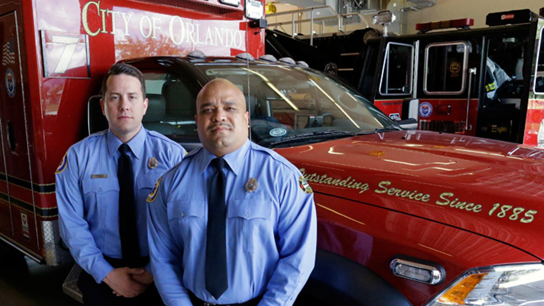 In this Thursday, June 30, 2016 photo, Josh Granada, left, and Carlos Tavarez the first paramedic-firefighters to respond to the Pulse nightclub shooting stand by their emergency vehicle at their fire station in Orlando, Fla. They made five trips with 13 victims to a hospital emergency room just a few blocks away the evening of the shooting.(AP Photo/John Raoux)