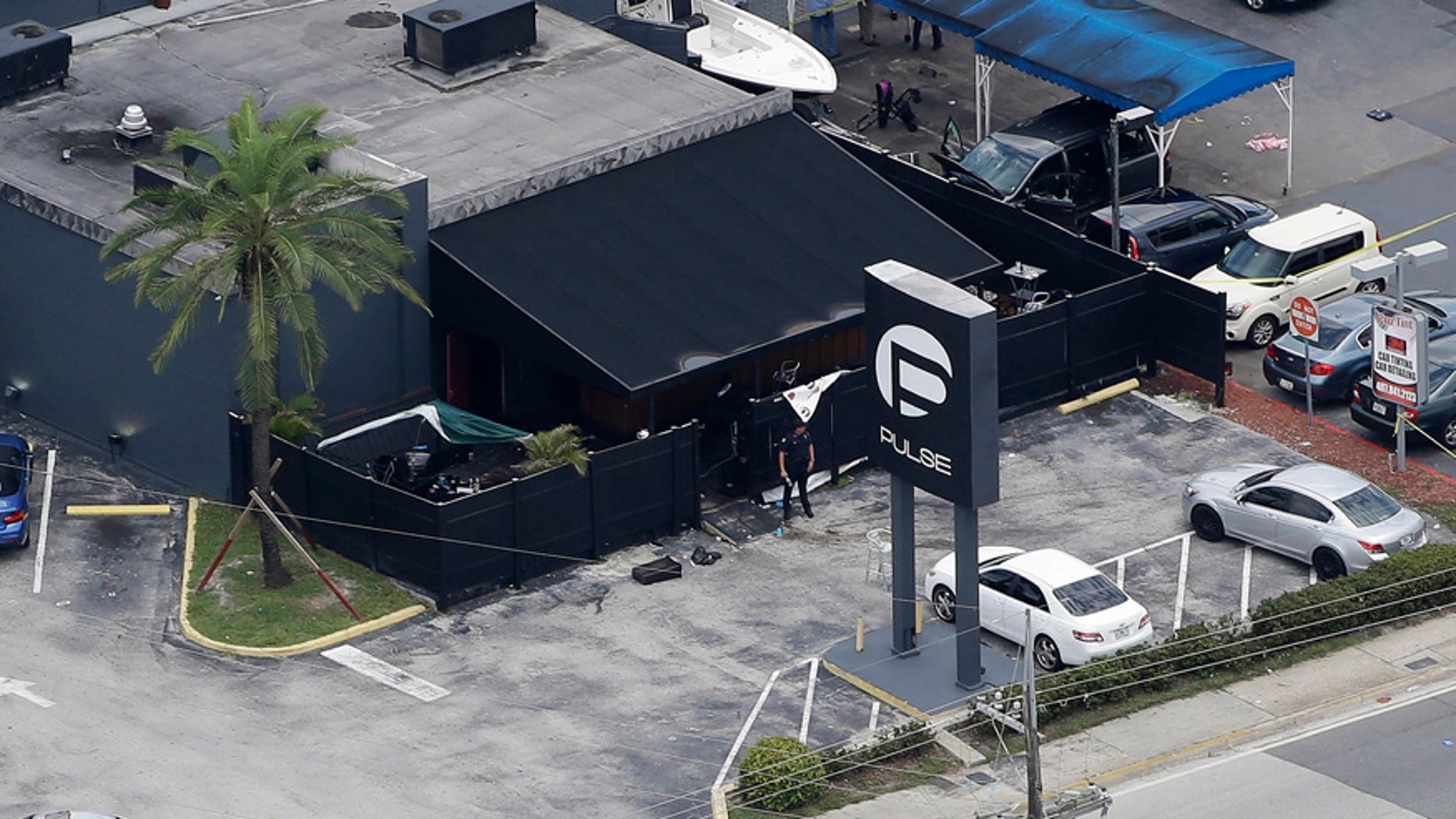 In this June 12, 2016 file photo, law enforcement officials work at the Pulse nightclub in Orlando, Fla., following a mass shooting.