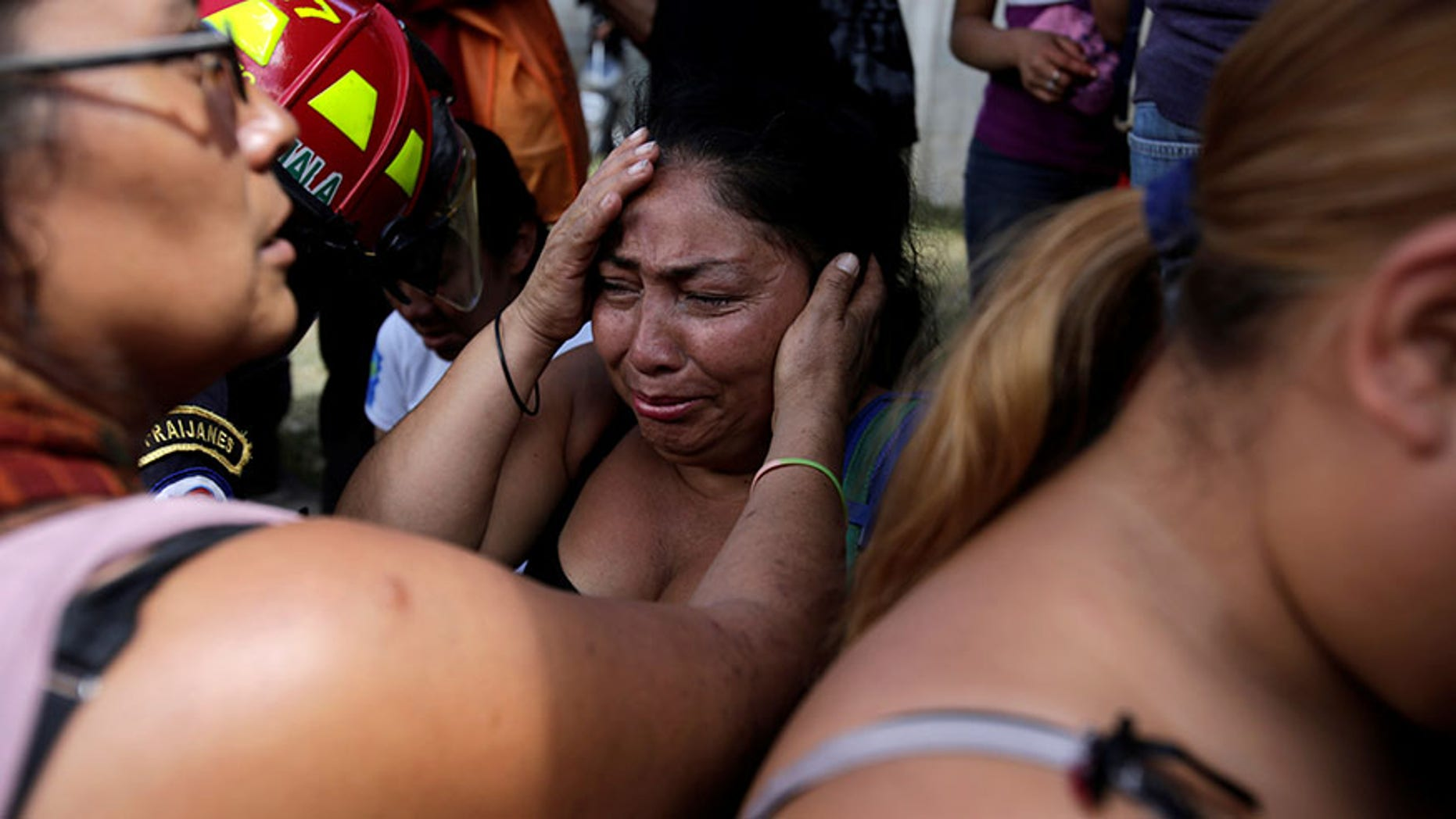 Family members wait for news of their loved ones after a fire broke at the Virgen de Asuncion home in San Jose Pinula, on the outskirts of Guatemala City, Guatemala March 8, 2017.