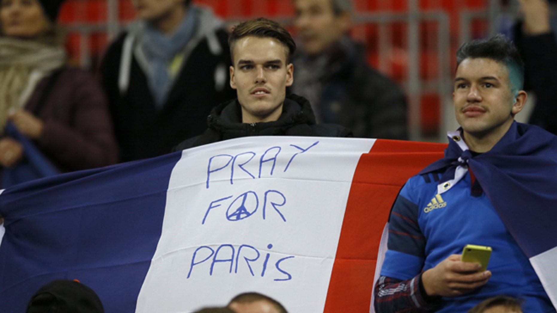 A man holds a French flag ahead of the international friendly soccer match between England and France at Wembley Stadium in London, Tuesday, Nov. 17, 2015. France is playing England at Wembley on Tuesday after the countries decided the match should go ahead despite the deadly attacks in Paris last Friday night which killed scores of people. (AP Photo/Kirsty Wigglesworth)