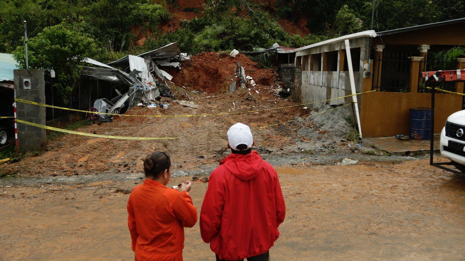 Civil Defense workers look the area where a couple was killed after their home was destroyed by a mudslide in Arraijan on the outskirts of Panama City, Tuesday, Nov. 22, 2016. Civil defense officials in Panama say the country has already seen three deaths blamed on late-season Tropical Storm Otto. (AP Photo/Arnulfo Franco)