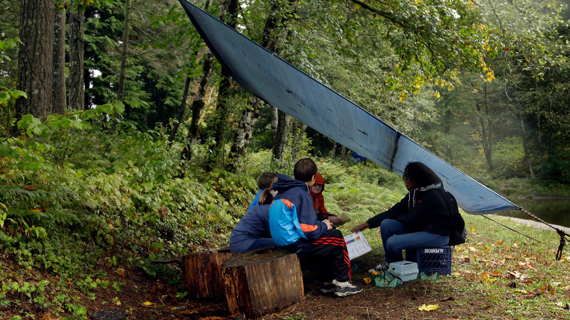 In this Oct. 6, 2016 photo, Outdoors School students gather for a lesson under a canopy in the forest at Camp Howard in Mount Hood National Forest near Corbett, Ore.