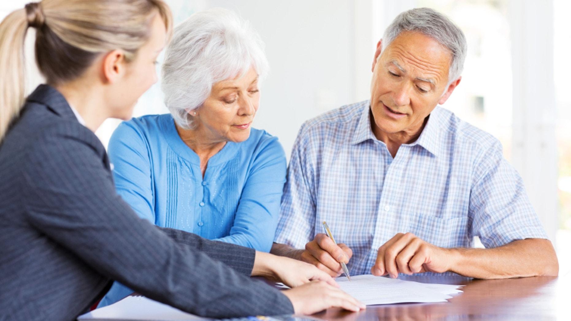 Financial advisor explaining investment plans to senior couple at home. Horizontal shot.