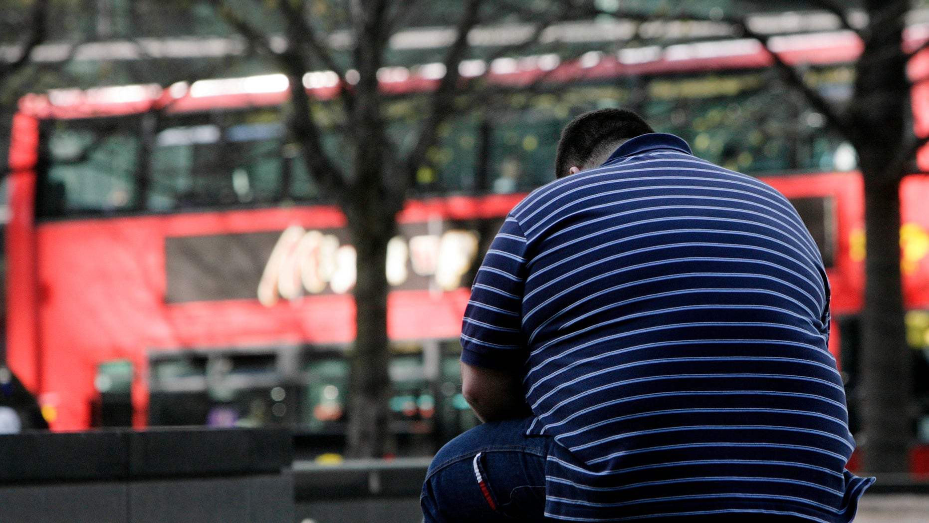 A man sits on a wall in the Canary Wharf financial district of London, April 1, 2009. (REUTERS/Simon Newman)