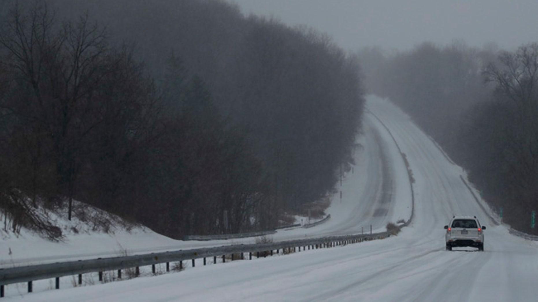 A car drives down US 30 through a winter snow storm, Tuesday, March 14, 2017, in Valley Township, Pa. (AP Photo/Matt Slocum)