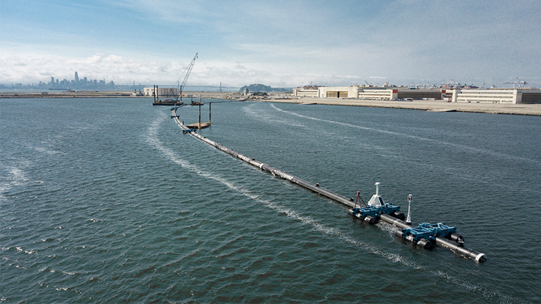 In this Monday, Aug. 27, 2018 photo provided by The Ocean Cleanup, a long floating boom that will be used to corral plastic litter in the Pacific Ocean is assembled in Alameda, Calif. Engineers will deploy a trash collection device to corral plastic litter floating between California and Hawaii in an attempt to clean up the world's largest garbage patch. The 2,000-foot long floating boom will be towed Saturday, Sept. 8, 2018, from San Francisco to the Great Pacific Garbage Patch, an island of trash twice the size of Texas.