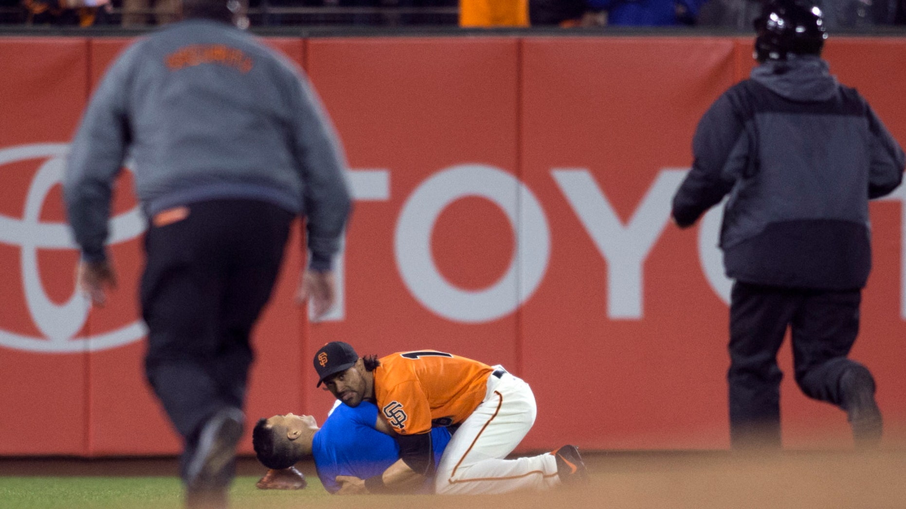 Sept. 30, 2016: San Francisco Giants' Angel Pagan (16) holds down a man who ran onto the field during the fourth inning of the Giants' baseball game against the Los Angeles Dodgers.