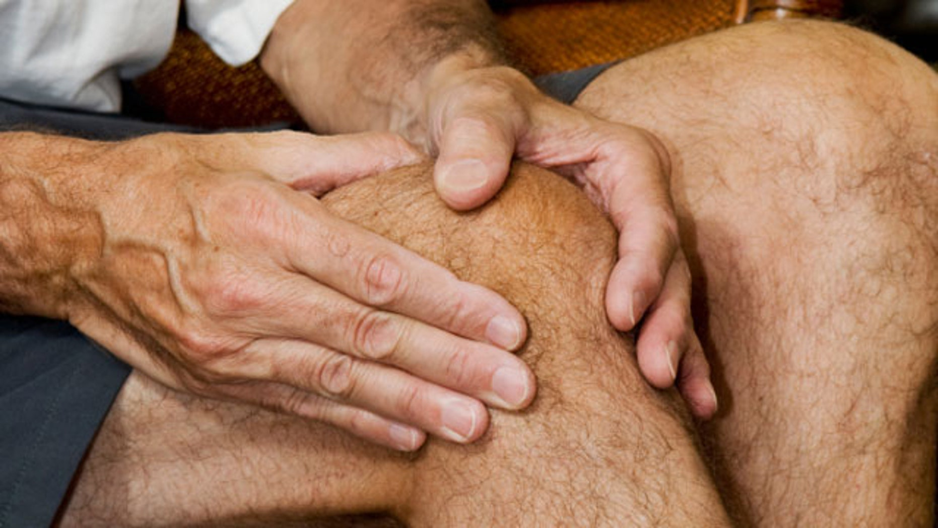 man massaging knee with apparent pain