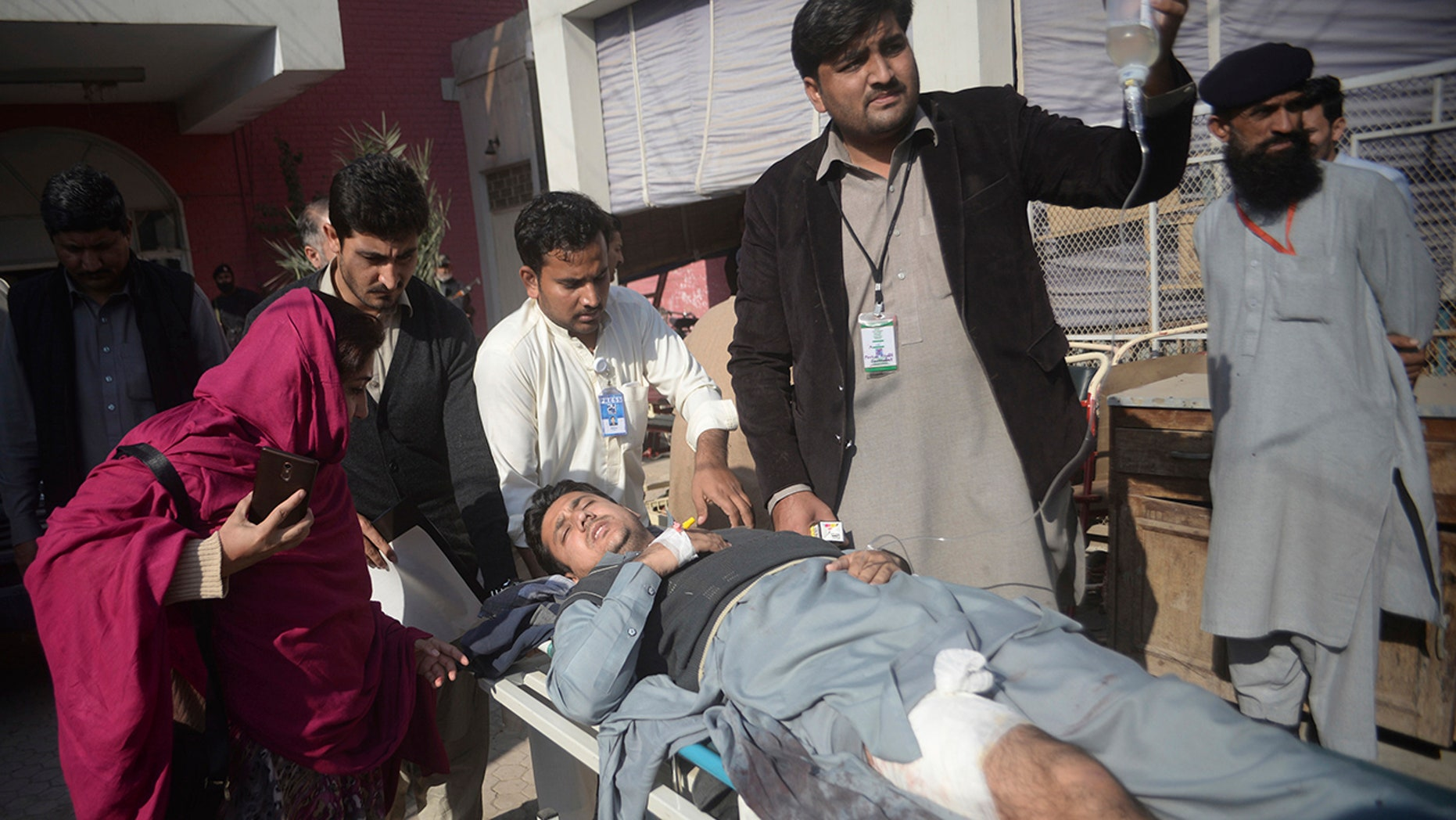 Dec. 1, 2017: Staff rush a man to a hospital after being injured during a crackdown operation against militants who stormed the agriculture institute in Peshawar, Pakistan.