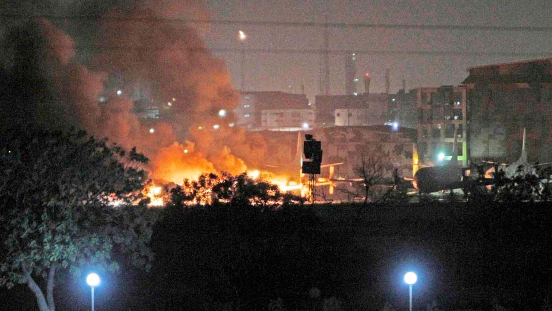 Humo y llamas se elevan desde una base de aviación naval  después de un ataque de milicianos en Karachi, Pakistán el domingo 22 de mayor del 2011. Al menos seis marinos y un paramilitar fueron muertos y 14 heridos en el enfrentamiento en la Estación Naval de Mehran que se prolongó más de cuatro horas, dijo el vocero de la Armada paquistaní, Irfan ul Haq. (Foto AP/Shakil Adil)