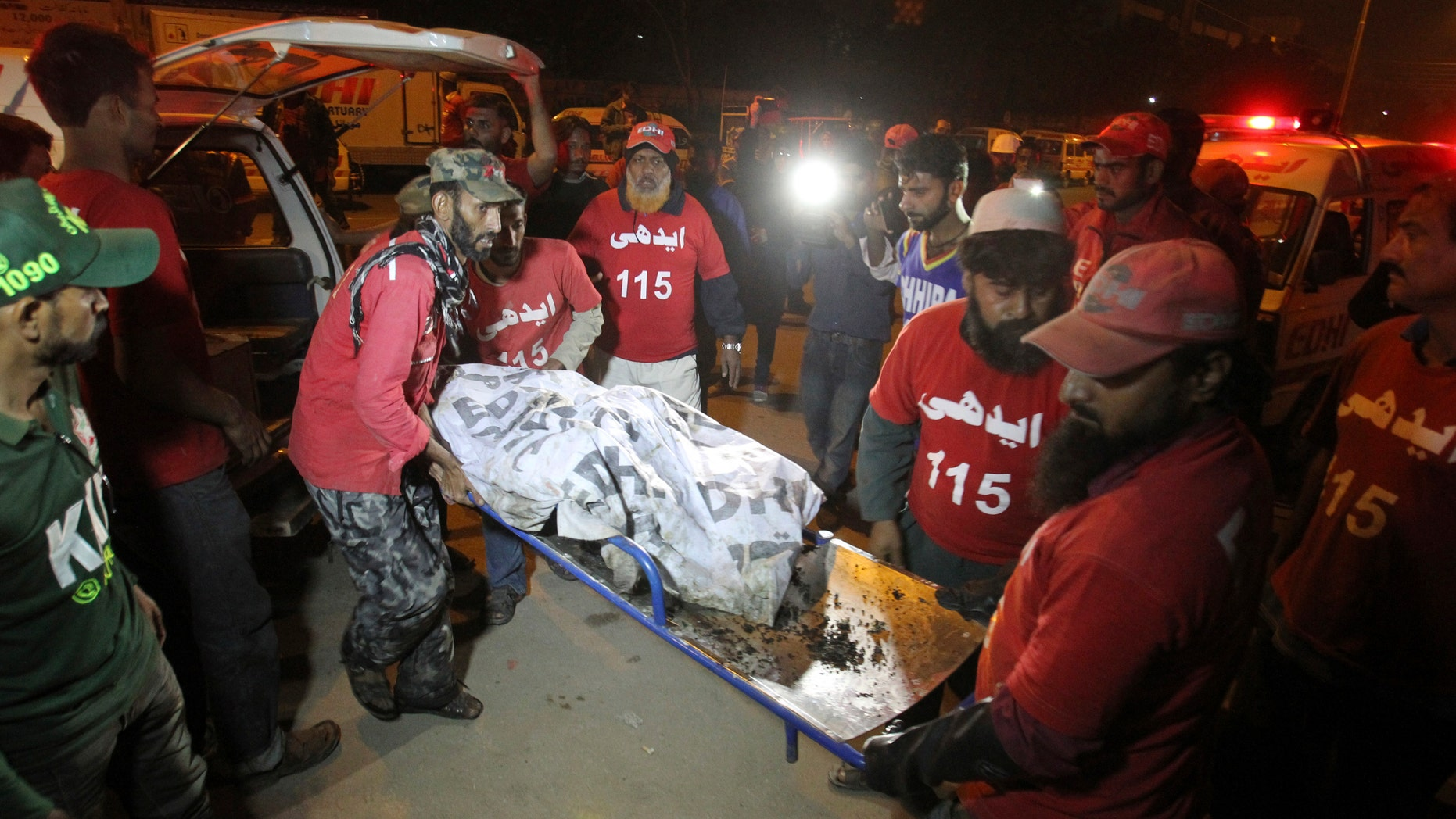 Jan. 11, 2015: Pakistani rescue workers carry the lifeless body of a bus accident victim to a hospital in Karachi, Pakistan.