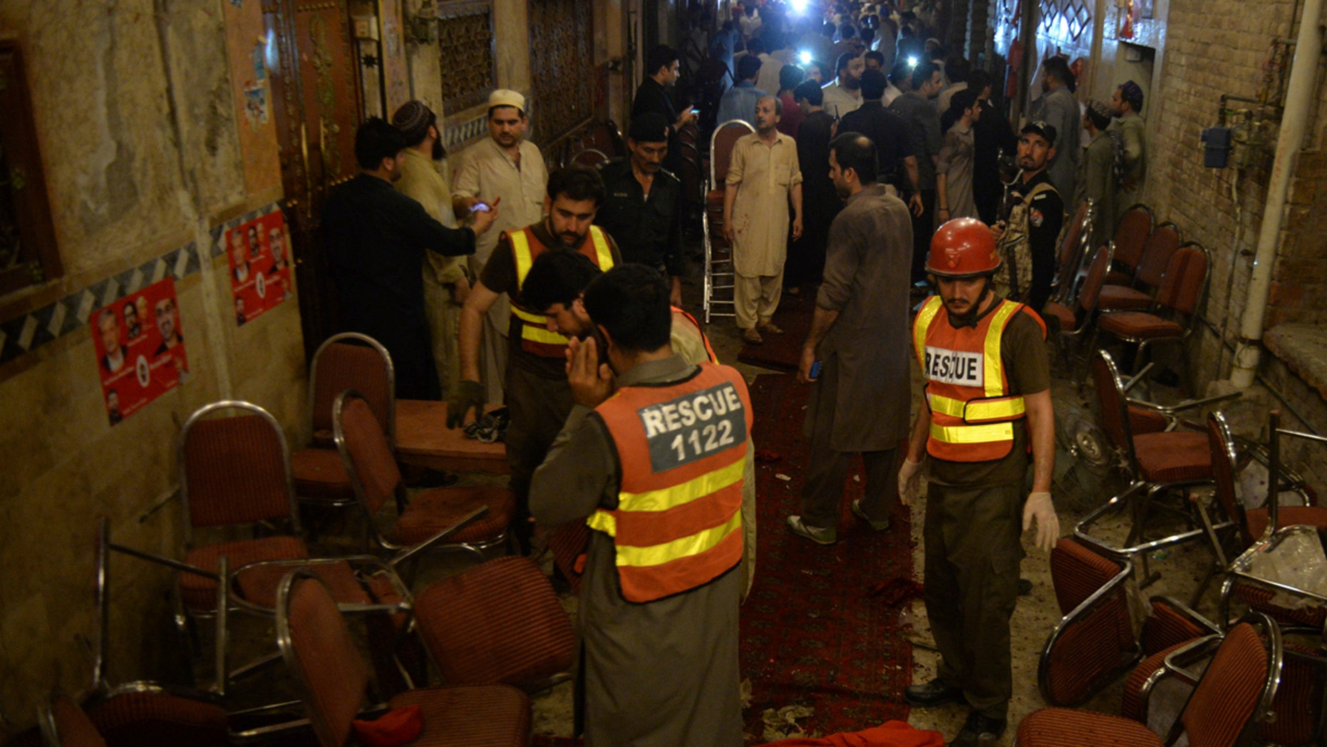 Pakistani rescue volunteers visit at a site of blast in Peshawar, Pakistan, Tuesday, July 10, 2018. Police in Pakistan say a suicide bomber has killed a secular party leader and many supporters during an election rally in the northwestern city of Peshawar. (AP Photo/Muhammad Sajjad)