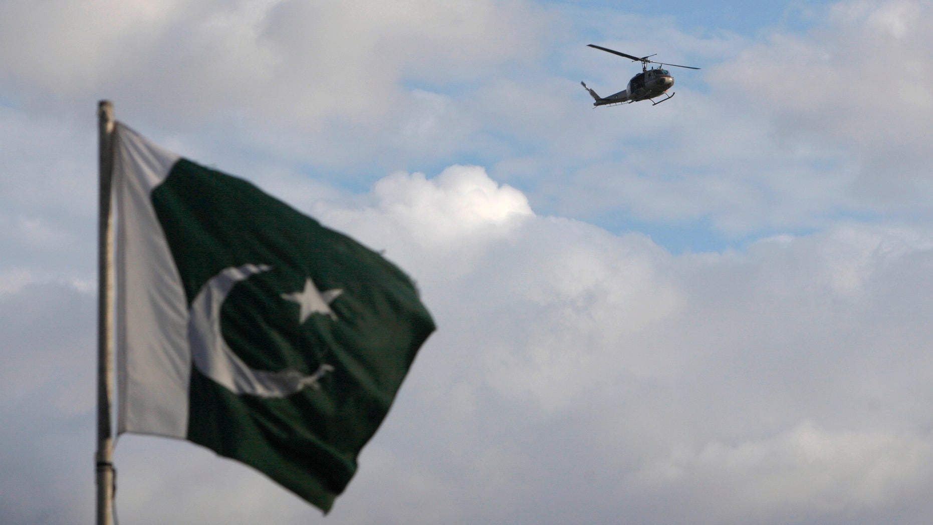 Sept. 2, 2014: A helicopter flies past a Pakistan's national flag in the premises of parliament house during the Revolution March in Islamabad