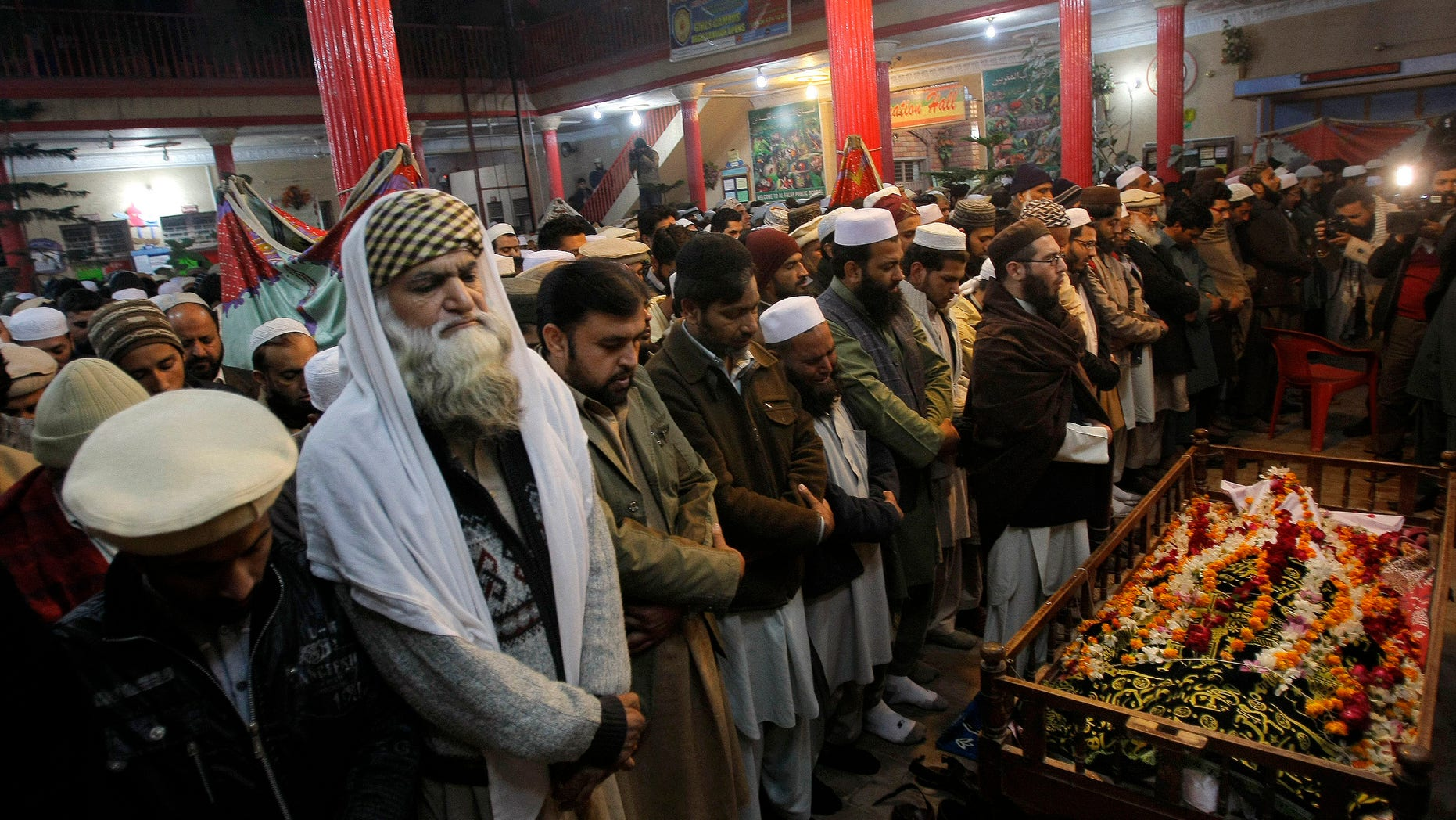 Dec. 16, 2014: Mourners and relatives of Pakistani teacher, Saeed Khan, a victim of a Taliban attack in a school, pray around his body, during his funeral procession in Peshawar, Pakistan.