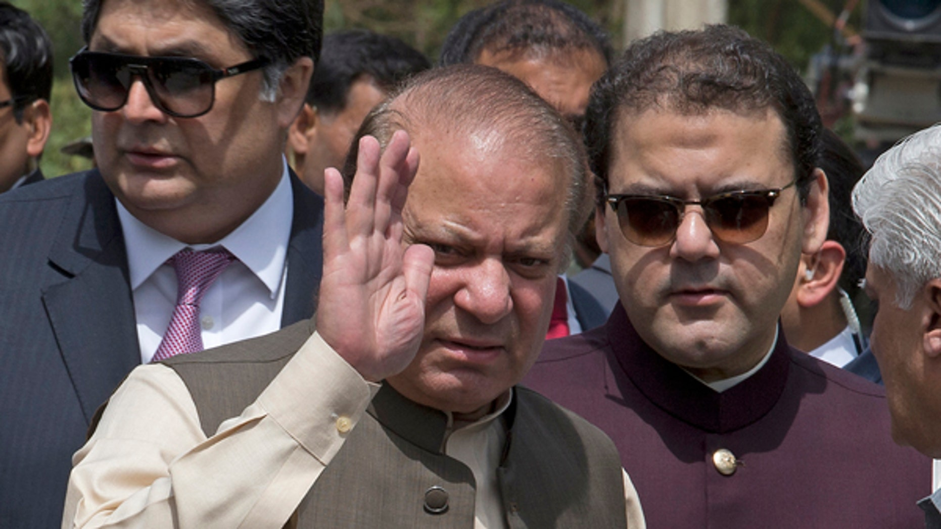 Pakistani Prime Minister Nawaz Sharif waves with his son Hussain Nawaz, right, outside the premises of the Joint Investigation Team, in Islamabad, Pakistan.