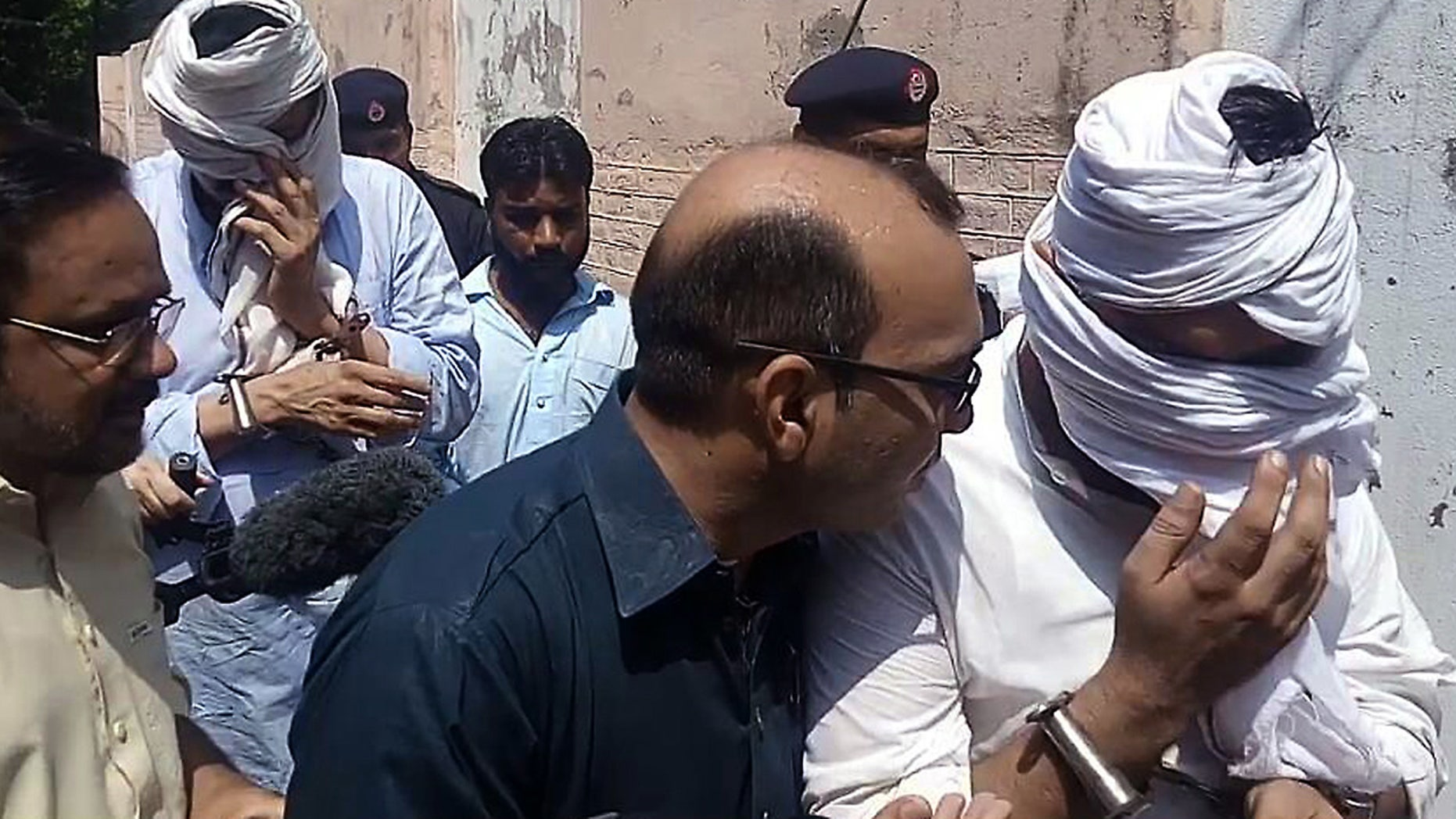 In this Monday, Sept. 5, 2016 photo, Pakistani police officers escort the detained father, second left face covered, and husband, right face covered, of slain British women Samia Shahid, to appear in court in Jhelum, in eastern Pakistan, Wednesday, Sept. 7, 2016.