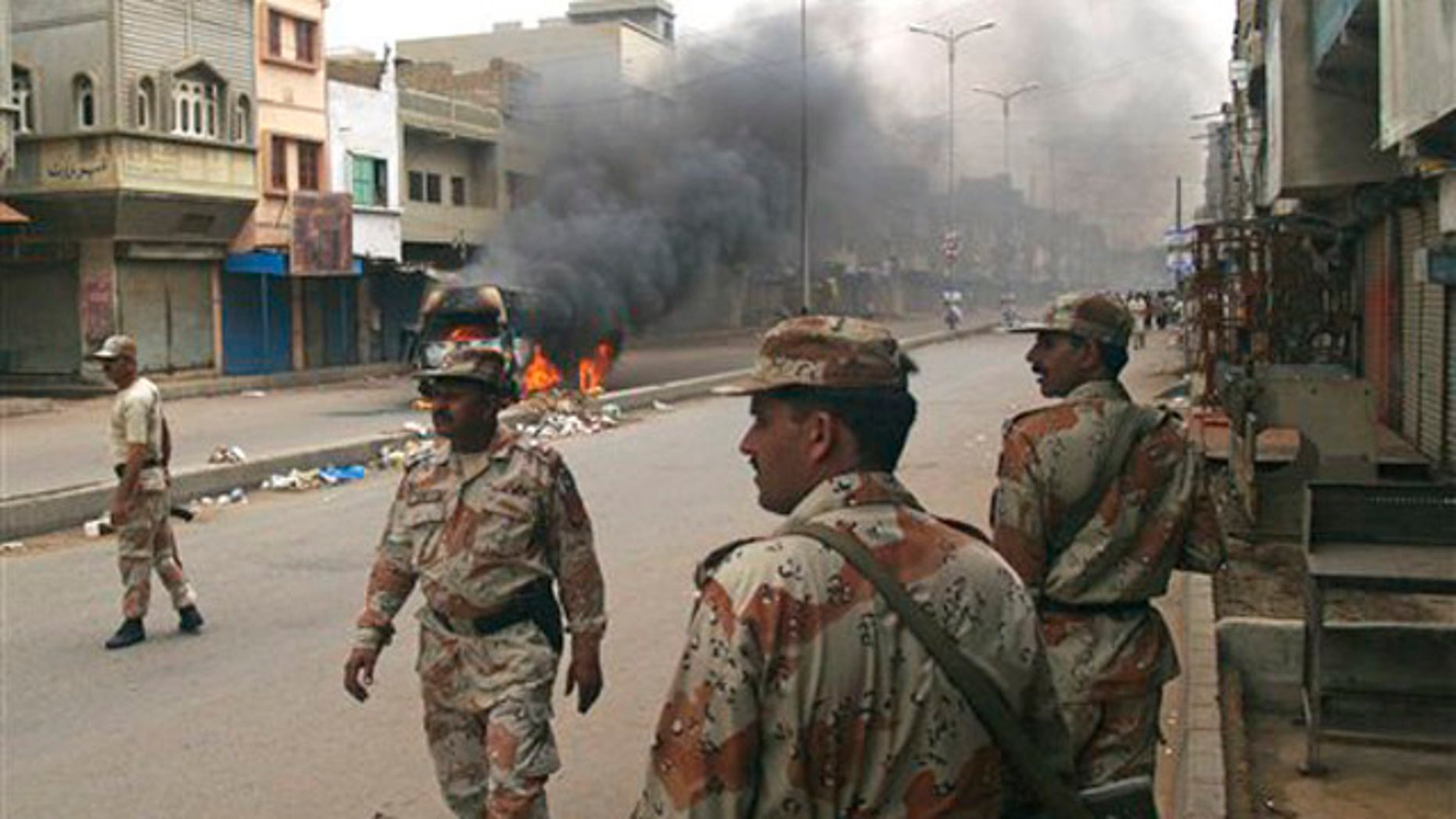 Pakistani para military troops gather near a vehicle set on fire by angry mob following the killing of a local leader of the Muttahida Quami Movement in Pakistan on Tuesday, Aug. 3, 2010. Gunmen killed dozens of people in Pakistan's largest city after the assassination of a lawmaker.