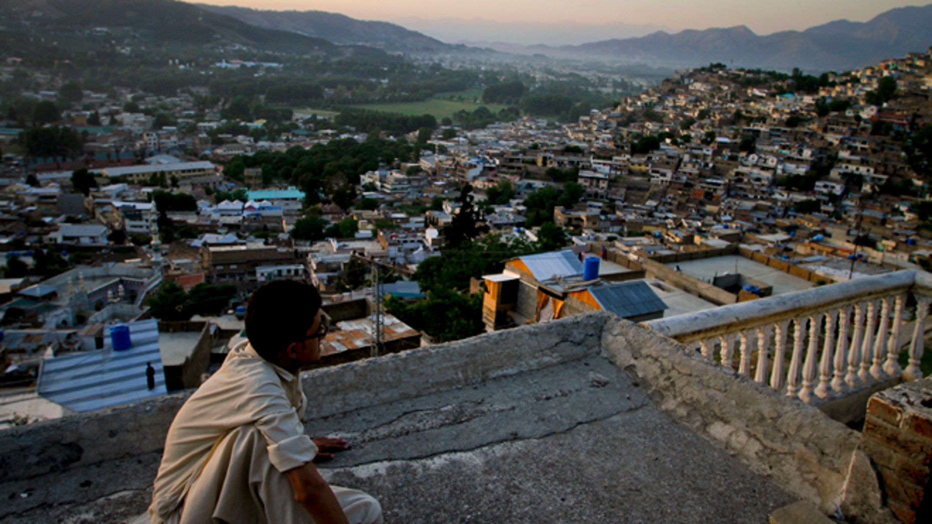 In this May 15, 2011 file photo, Ali Raza sits on the rooftop of his house as he views the city of Abbottabad, Pakistan. Pakistani officials say the government plans to build a recreation complex in the town.