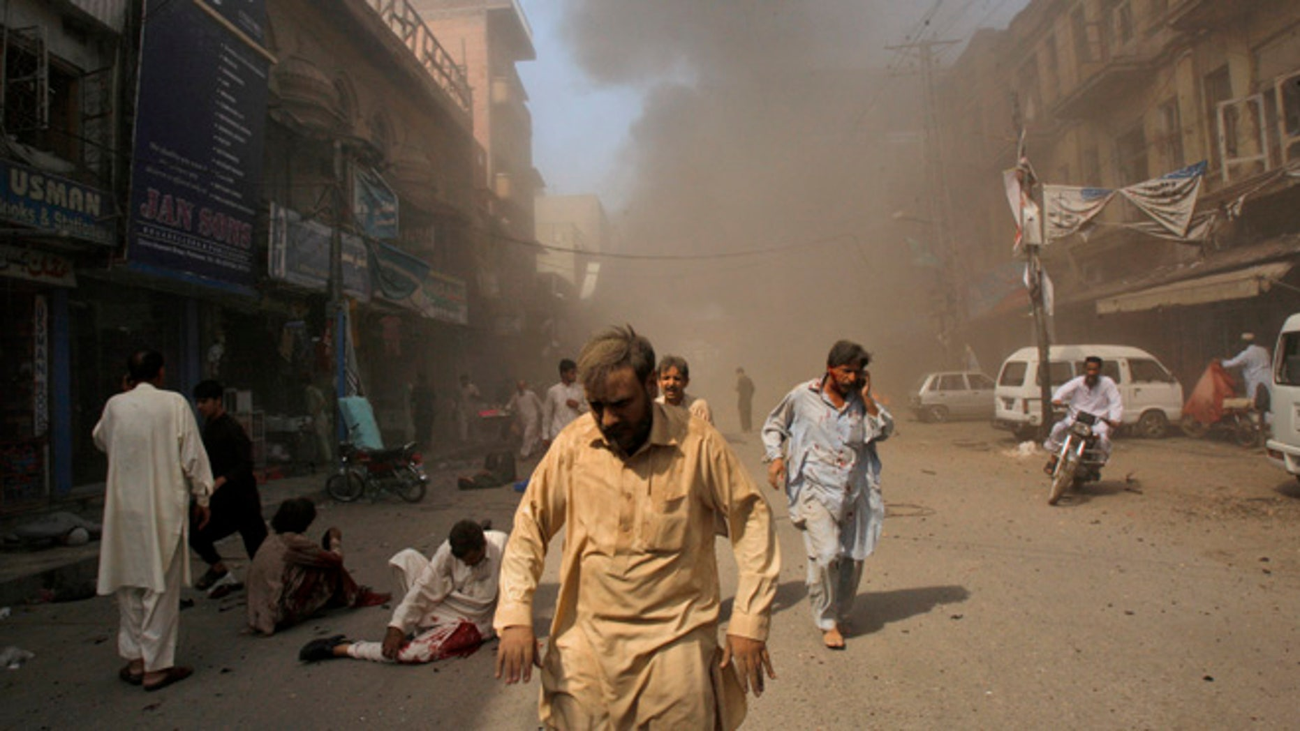 Sept. 29, 2013: Pakistani men rush away from the site of a blast shortly after a car explosion in Peshawar, Pakistan. A car bomb exploded on a crowded street in northwestern Pakistan Sunday, killing scores of people in the third blast to hit the troubled city of Peshawar in a week, officials said.