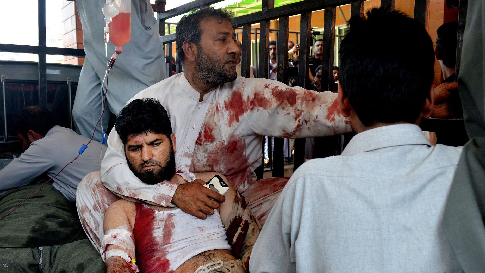 Volunteers carry an injured man to a hospital in Peshawar, Pakistan.