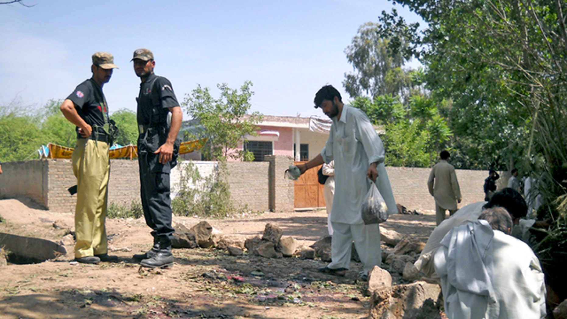 Pakistani police officers and rescue worker inspect the site of homicide bombing in Kacha Pukka area near Kohat, Pakistan. (AP)