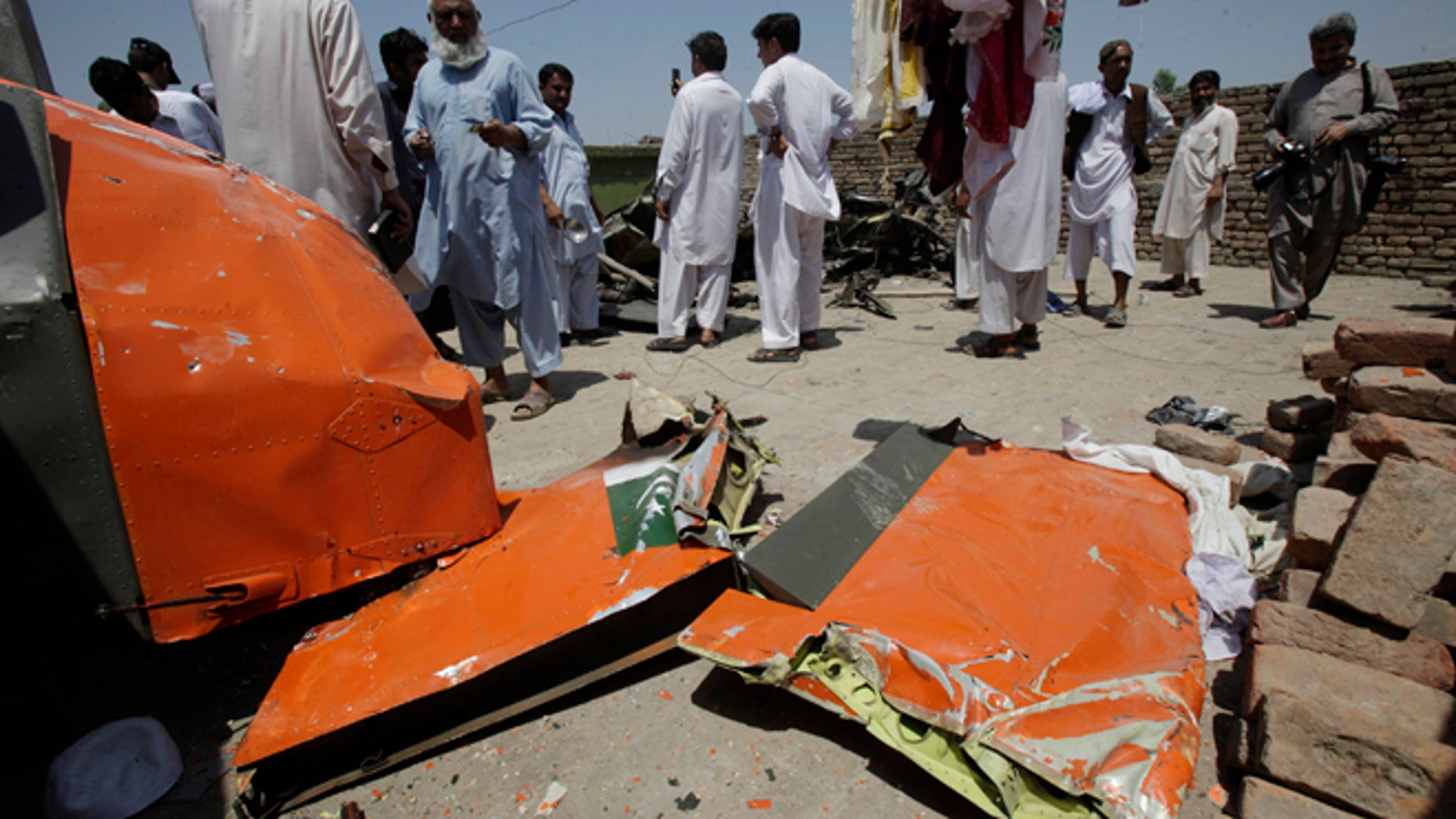 May 17, 2012: People on a rooftop look at a wreckage of a plane which crashed in Nowshera, 21 miles east of Peshawar, Pakistan.
