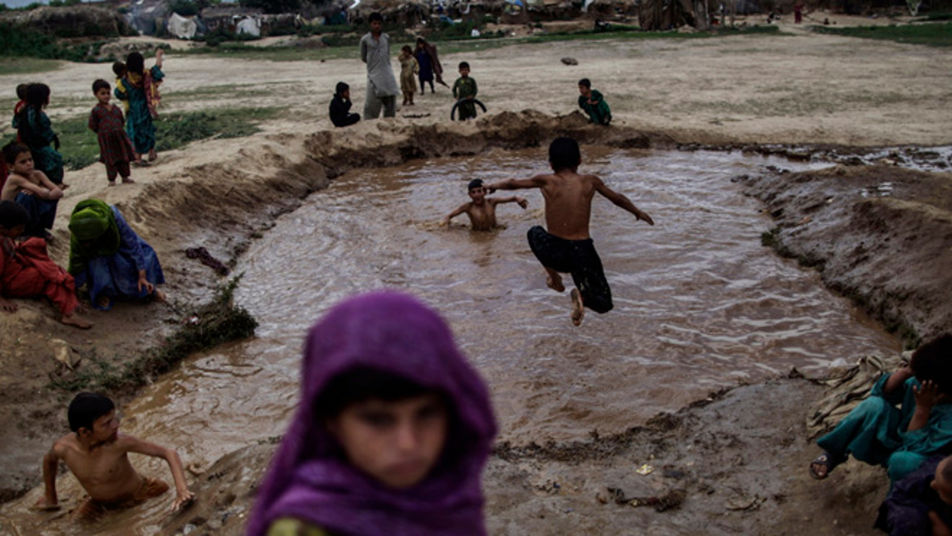 June 17, 2013: Afghan refugee children, swim in muddy water created from a broken water pipe, on the outskirts of Islamabad, Pakistan. Pakistan hosts over 1.6 million registered Afghans, the largest and most protracted refugee population in the world, according to the U.N. refugee agency.