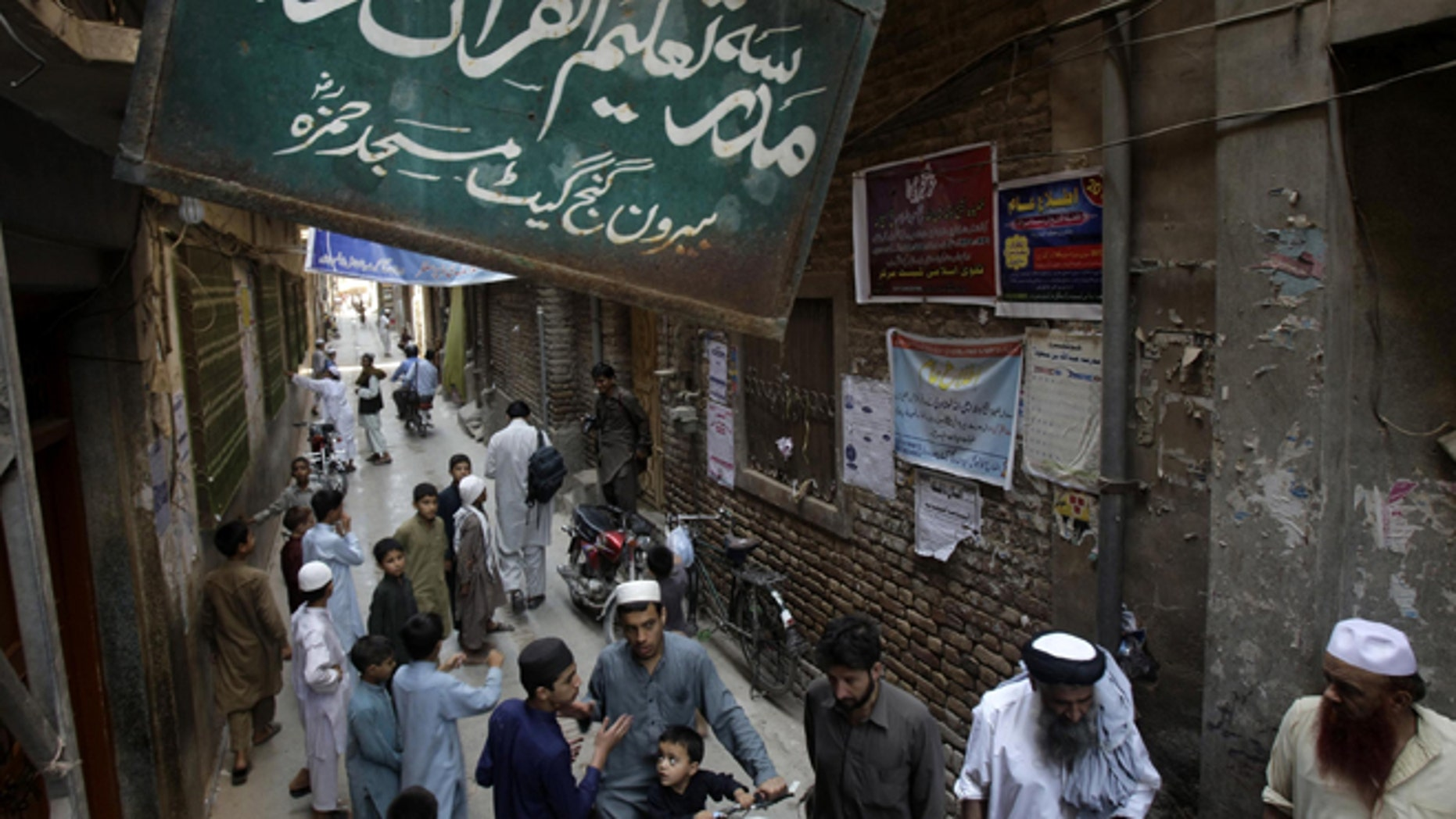 """Aug. 21, 2013: People gather outside the Jamia Taleem-Ul-Quran-Wal-Hadith Madrassa, in Peshawar, Pakistan. The United States has placed unprecedented sanctions on an Islamic school in northwest Pakistan for allegedly training and financing fighters from Al Qaeda and other militant groups. Board on top reads """"school for Koran and Hadith studies."""""""