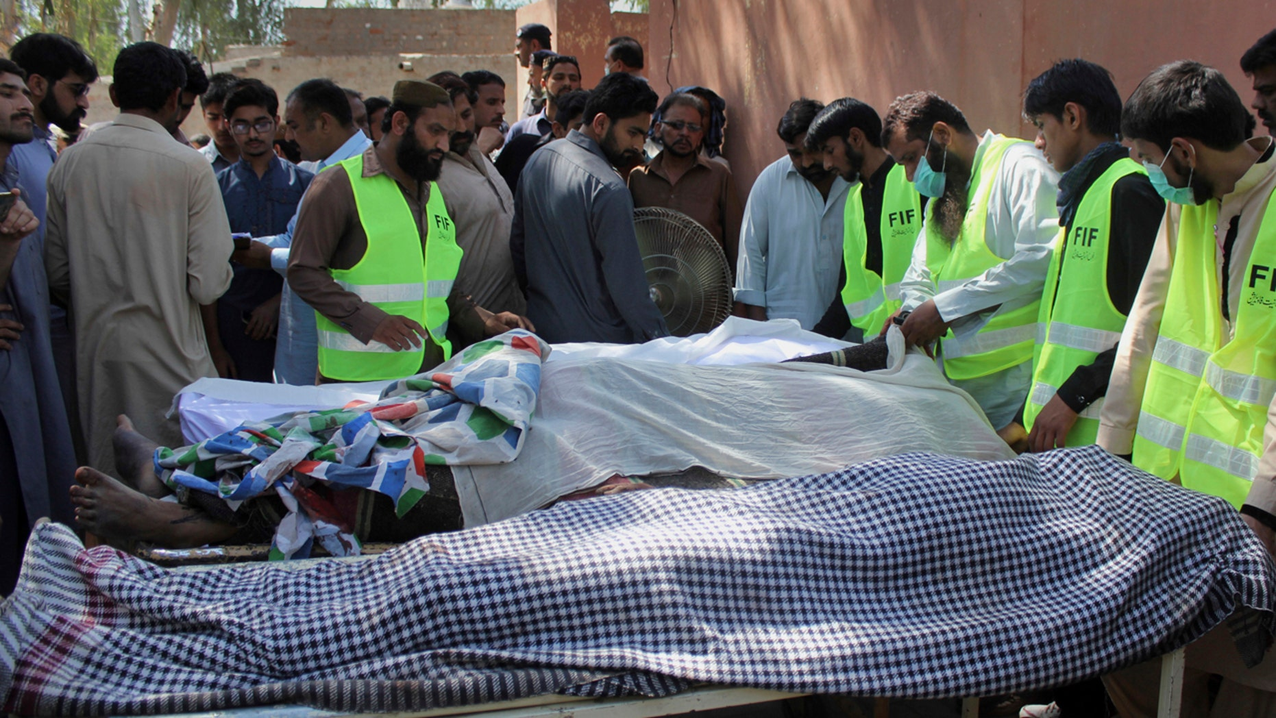 Pakistani volunteers and local residents gather around the bodies of people who were killed in a local shrine, outside the morgue of a hospital in Sarghodha, Pakistan, Sunday, April 2, 2017.