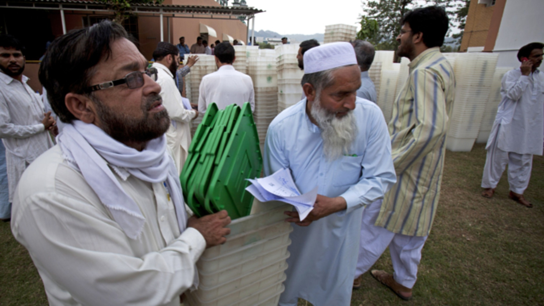 May 10, 2013: Pakistani election staff carry ballot boxes for tomorrow;s elections in Islamabad, Pakistan.