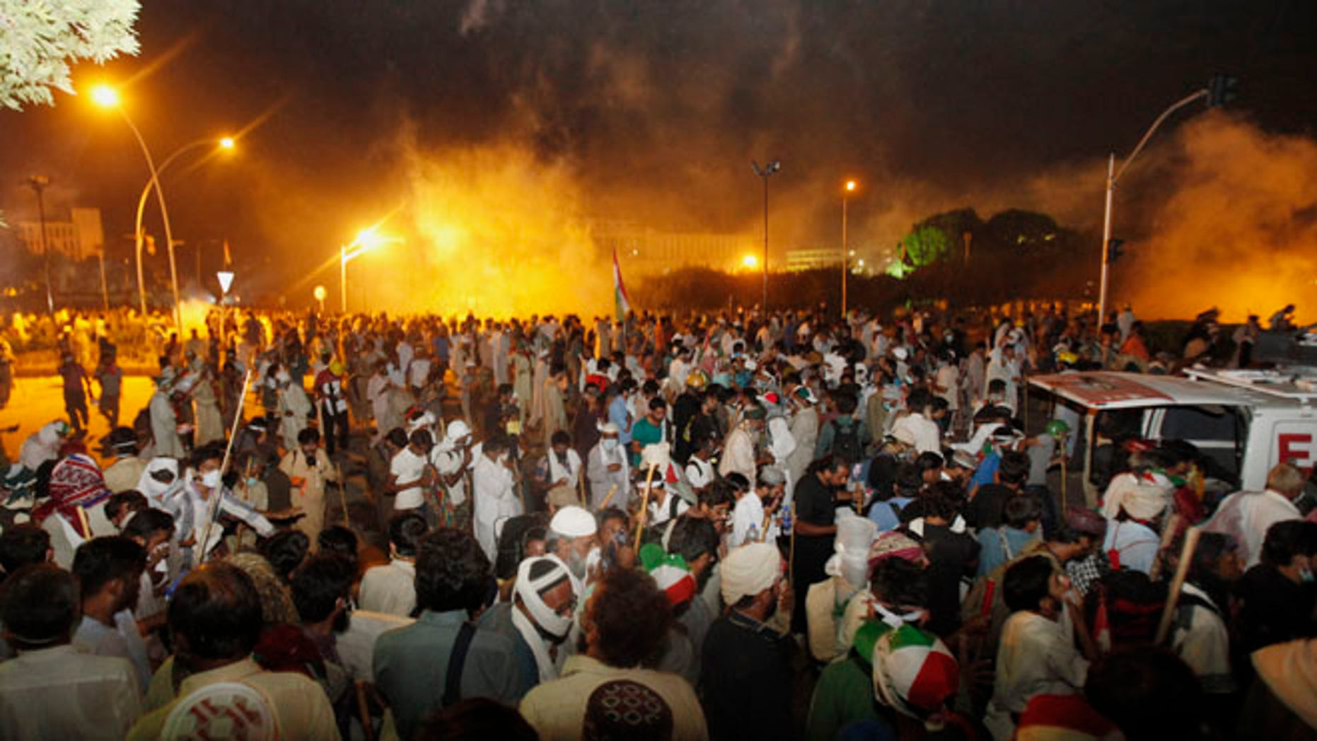 Aug 30, 2014: Pakistani protesters run after police fire tear gas during clashes near the prime minister's home in Islamabad, Pakistan. (AP)