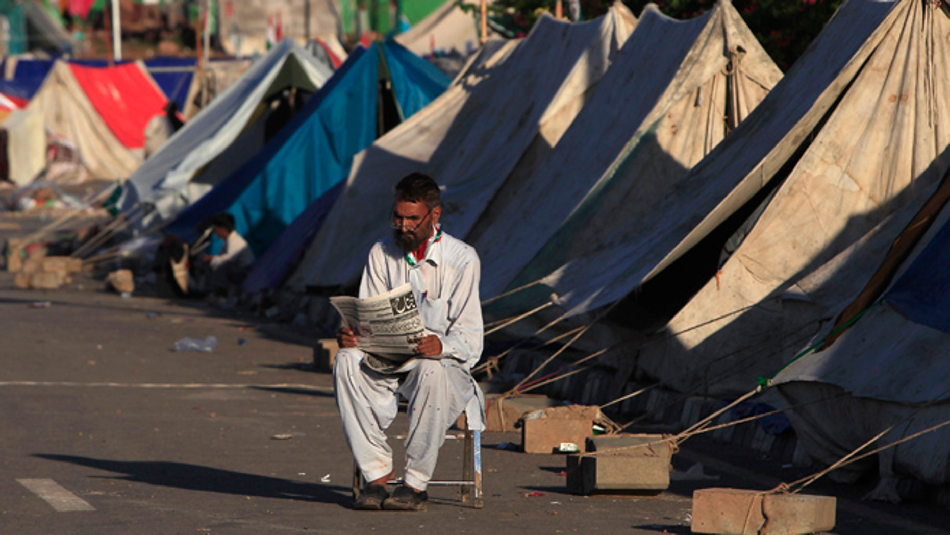 Sept. 7: An anti-government protester reads a newspaper as he sits outside makeshift tents, set up in front of the Parliament House during the Revolution March in Islamabad.