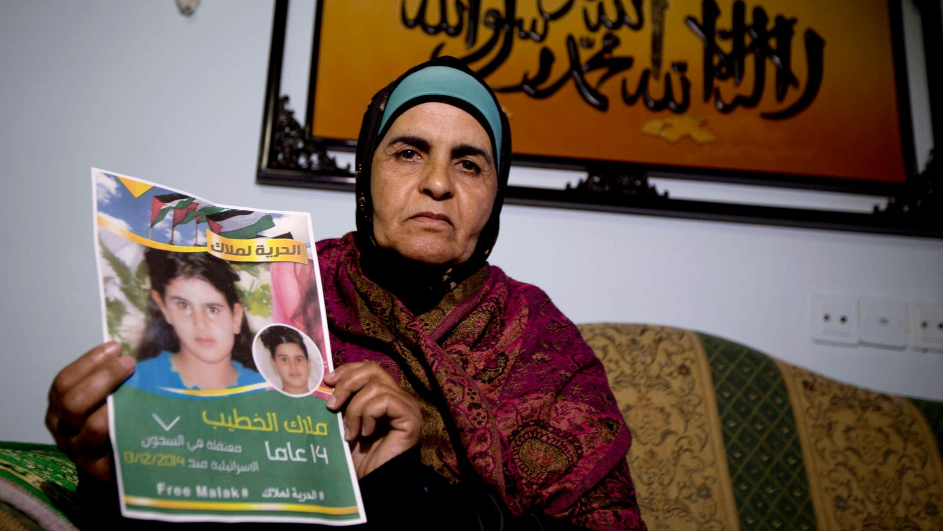 Jan. 27, 2015: Palestinian Khawla Al-Khatib, holds a poster of her 14-year-old daughter Malak al-Khatib, detained in Israel, in the village of Beitin near the West Bank city of Ramallah.